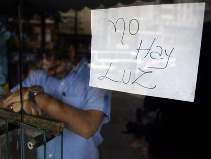 """""""No electricity"""" reads a sign in a closed shop in Caracas."""