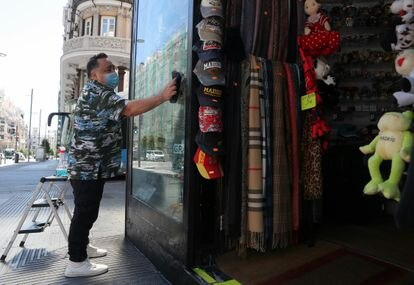 A worker cleans the window to a store in the center of Madrid.