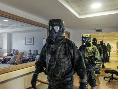 Members of the military arrive at a residence in Alcalá de Henares, Madrid, to carry out disinfections.