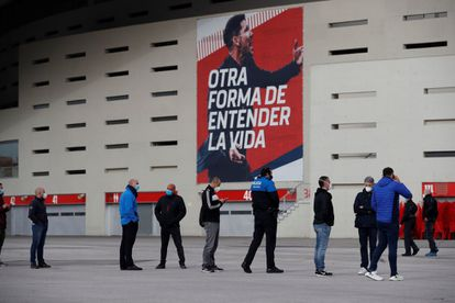 People wait in line to be vaccinated outside the Wanda Metropolitano stadium in Madrid at the end of February.