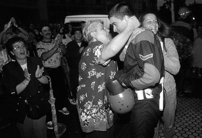 A woman hugs a member of the Basque regional police (Ertzaintza) who has removed his head gear and is showing his face during the unrest in Ermua.