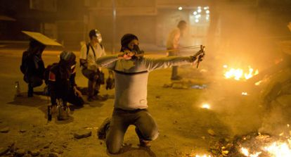 Protestors in Caracas set up street barricades and fire slingshots at police.