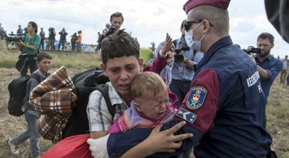 Refugees are stopped by police in Hungary on September 8.