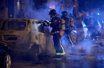 Firefighters put out fires set by protesters in Barcelona.