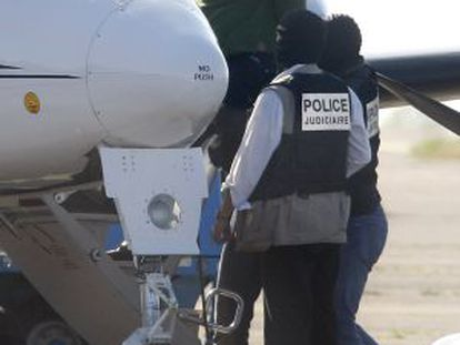 French police lead arrested ETA leader Mikel Carrera into an airplane in Biarritz.