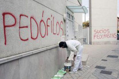 A painter begins to remove spray-painted messages in San Juan María Vianney parish, Granada.