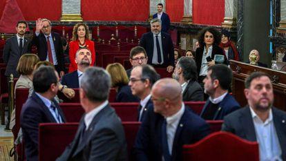 Catalan premier Quim Torra waves at the defendants inside the Supreme Court.