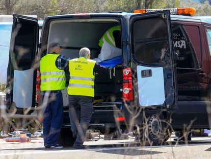 Authorities place the body of a victim into a hearse on the Spanish AP-7 motorway near Freginals.