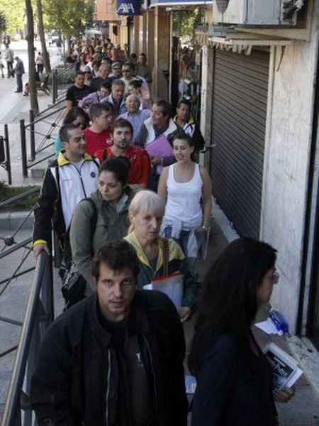Jobseekers stand in line outside an employment agency in Getafe.