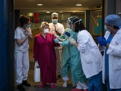 Health workers in Barcelona applaud a coronavirus patient after she is discharged from hospital.