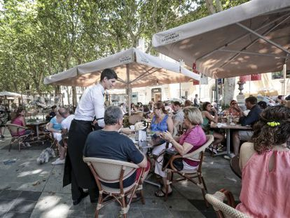Tourists enjoy drinks and snacks at a terrace bar in Palma de Mallorca.