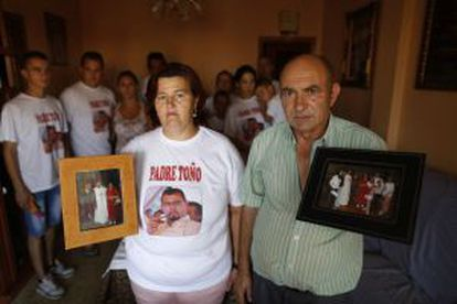 Father Toño's parents hold up photos of their son, with the rest of the family behind them.
