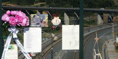 People leave flowers, messages and photos in memory of the train crash victims at the bridge over A Grandeira curve, in Angrois.