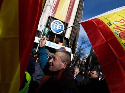 A taxi driver waves a Spanish flag outside the Popular Party (PP) headquarters in Madrid.