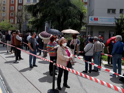 People wait in line for the Covid-19 vaccine outside Gregorio Marañón Hospital in Madrid.