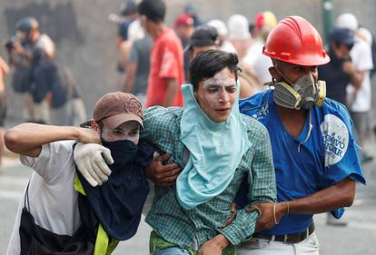 An injured demonstrator is assisted by others during clashes with government security forces in Caracas on Tuesday.
