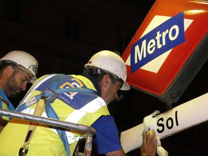 Workers replacing signage at Sol Metro station.