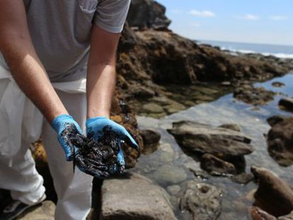 A volunteer clears up fuel oil on a beach in Mogán, Gran Canaria on Saturday.
