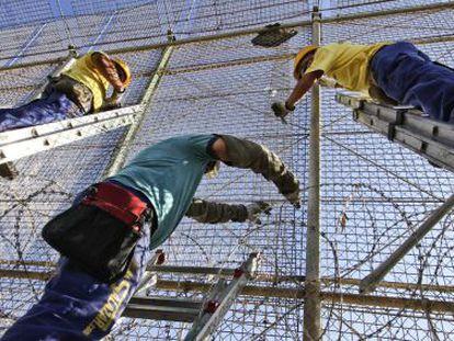 Technicians install the razor wire on the Melilla border fence.