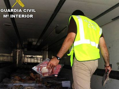 A Civil Guard officer inspects a truck containing expired ham.