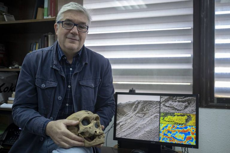 Fernando Muñiz, one of the researchers who discovered the Neanderthal's footprint, holds up a Neanderthal skull while displaying the evidence found in Gibraltar.