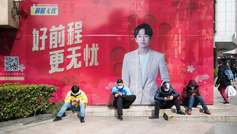Cuatro repartidores con mascarillas junto a una boca de metro en Shangai, el mes pasado.