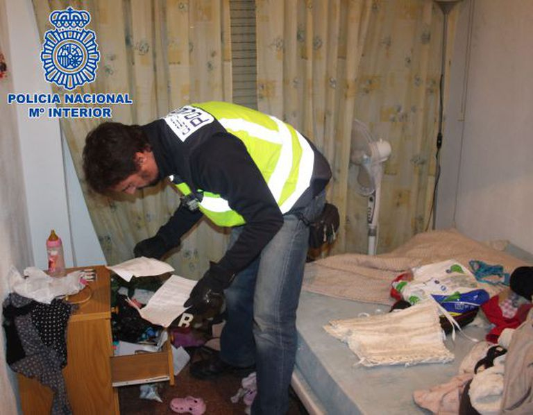 A police officer searches a home used by the prostitution ring.