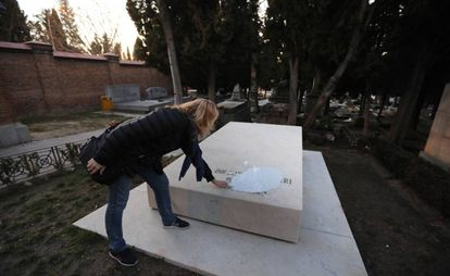 "Lola Ruiz-Ibárruri, granddaughter of ""La Pasionaria,"" inspects the white paint on her grandmother's tomb in La Almudena cemetery."