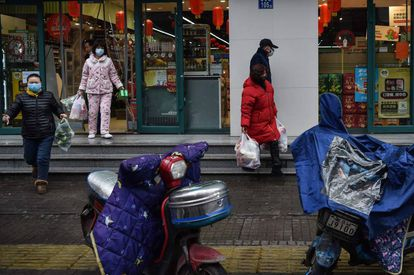 People wearing face masks leave after stocking up on food at a market in Wuhan on January 26.