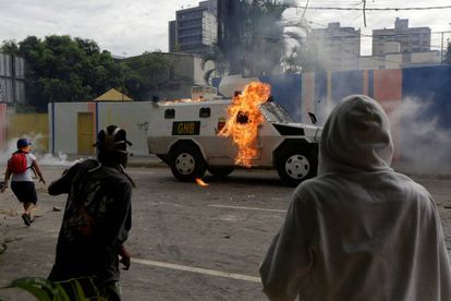 An armored police vehicle is hit by petrol bombs thrown by opposition supporters on Wednesday.