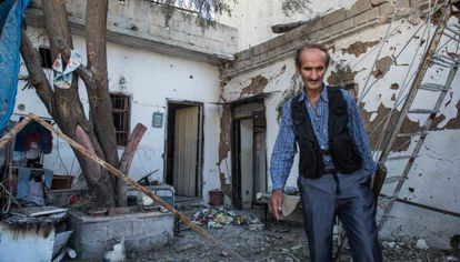 A member of the Kurdish security forces inspects a home reduced to rubble in Qamishli.