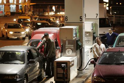 Drivers line up to fill their tanks at a gas station.