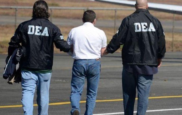 US Drug Enforcement Administration agents lead a suspect away.