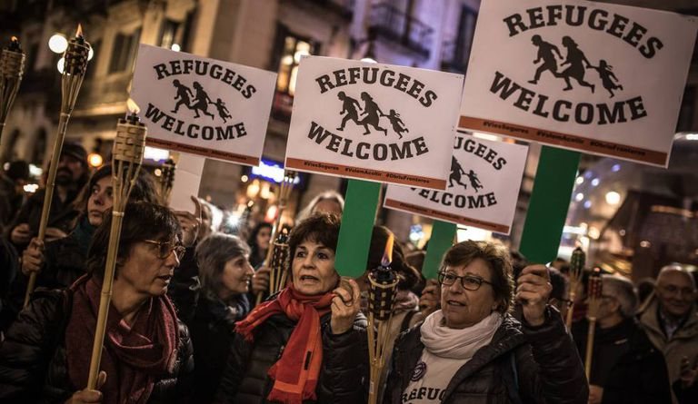 People in Barcelona march in support of refugees.