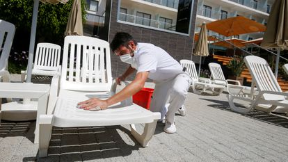 A worker wearing a protective face mask cleans a sunbed in a pool area of a hotel at Palma beach.