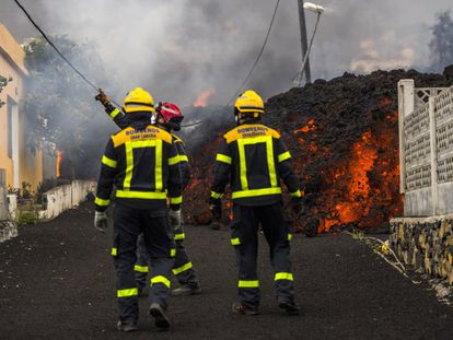 A group of firefighters face a lava flow in La Palma.