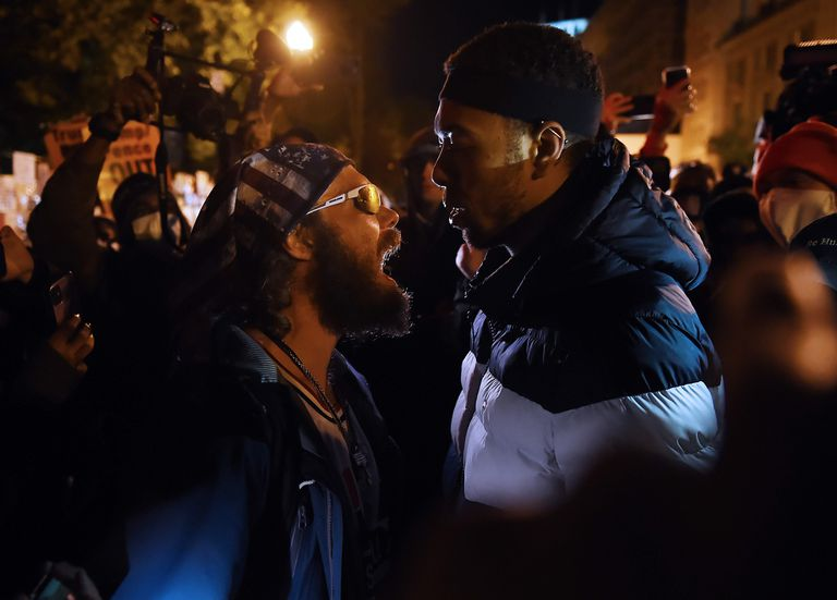 A Donald Trump supporter (l) clashes with a demonstrator at Black Lives Matter plaza across from the White House on election day in Washington, DC on November 3, 2020.