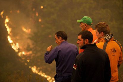 Residents watch on as a fires burns near the Os Ancares natural reserve.