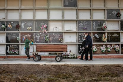 A coronavirus victim is laid to rest in Valencia, accompanied by family members.
