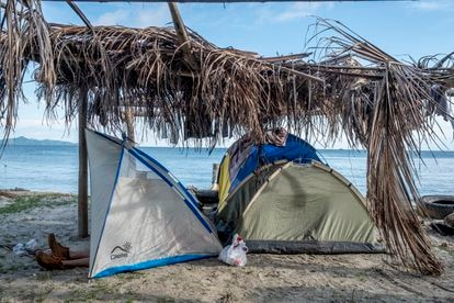A migrant rests in a tent on a beach in Necoclí.