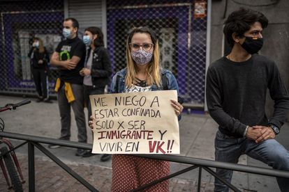 """A protester holds a sign with the message: """"I refuse to be confined solely for being an immigrant and living in Vallecas."""""""