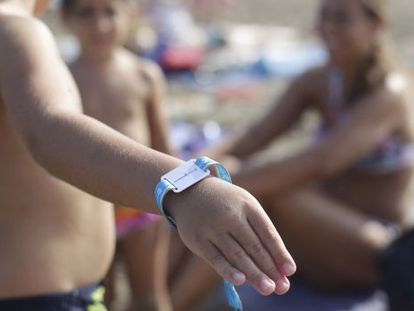 A child shows off his bracelet at a beach in Castellón.