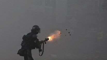 A police officer using tear gas against protesters marching against tax reform in Cali.