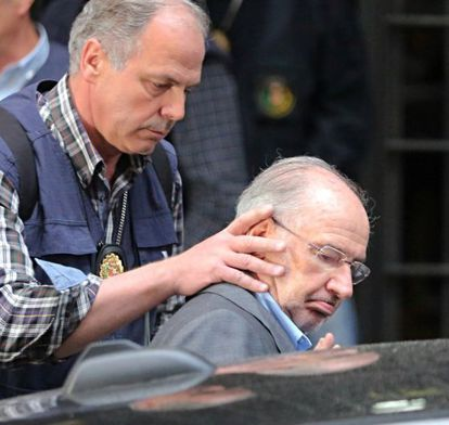 Rodrigo Rato is guided into a patrol car following his arrest on Thursday.