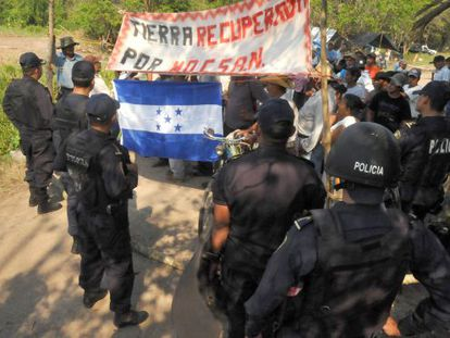 Police watch protestors take over a plot of land in Honduras.