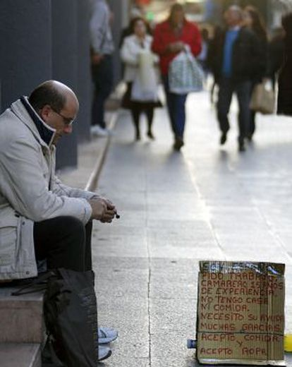 An out-of-work waiter begging on the streets of Valencia.