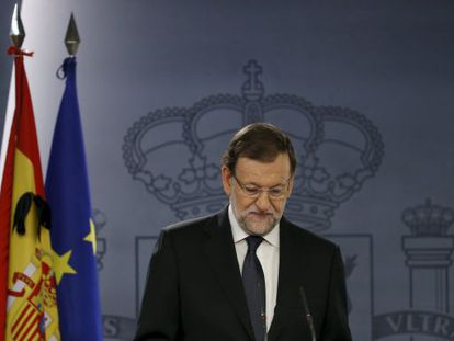 A black ribbon is seen on a Spanish flag as Prime Minister Mariano Rajoy speaks at La Moncloa.