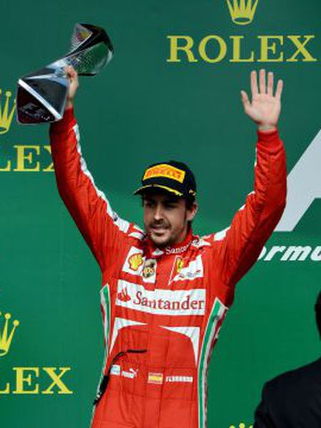Second-place finisher Ferrari driver Fernando Alonso holds the trophy on the podium after the Canadian Grand Prix.
