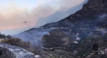 Houses dot the hillside as a helicopter flies to drop water over wildfires at Artenara, Gran Canaria.
