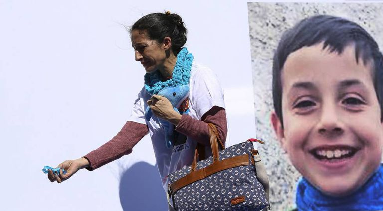 Patricia Ramírez passes by a photo of her son, victim Gabriel Cruz, at a protest for the return of the child.